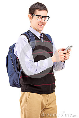 Smiling student with backpack typing a sms on a phone