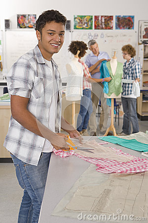 Free Smiling Student Cutting Fabric In Home Economics Classroom Stock Images - 41719494