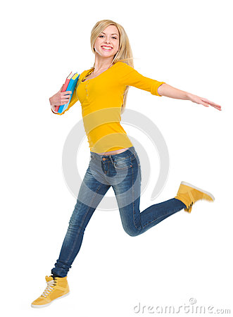 Smiling student girl with books jumping