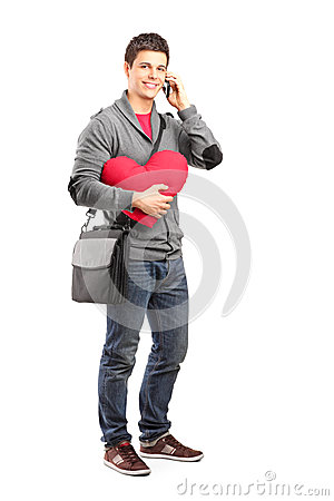 Smiling student holding a heart and talking on a phone