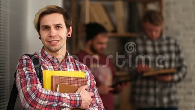 Smiling student standing with bag and notebooks stock video