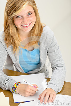 Smiling student teenager sitting behind desk write