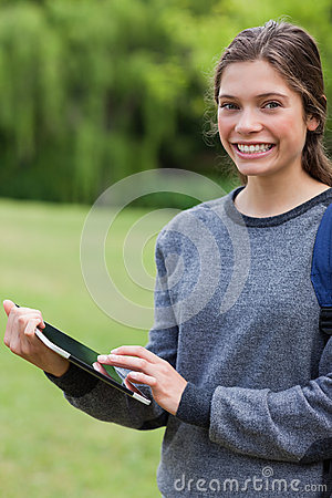 Smiling student using her tablet pc while standing