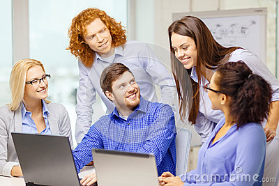 Smiling team with laptop computers in office