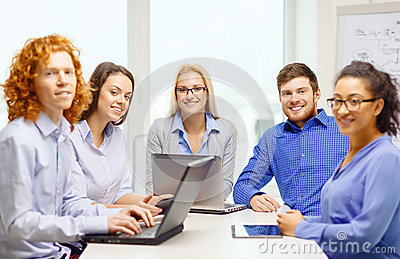 Smiling team with laptop and table pc computers