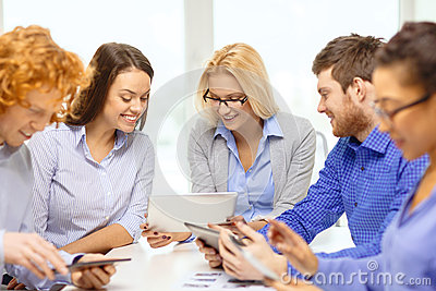 Smiling team with table pc and papers working