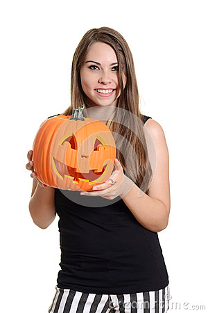 Smiling teen girl with a pumpkin
