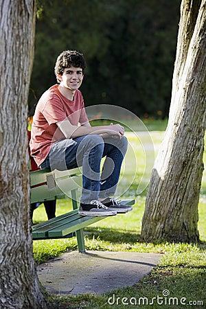 Smiling Teenage Boy Sitting on Bench