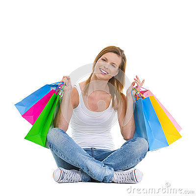 Smiling teenage girl sitting with shopping bags