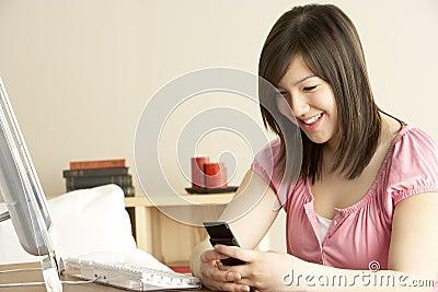 Smiling Teenage Girl using Mobile Phone at Home