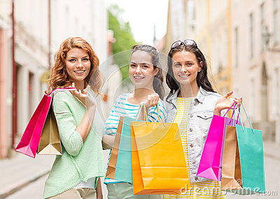 Smiling teenage girls with shopping bags on street