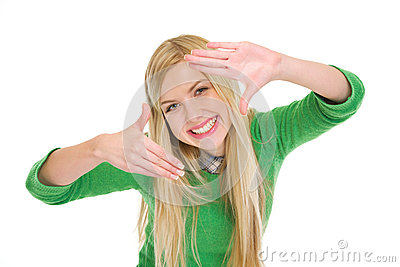 Smiling teenage student girl framing with hands