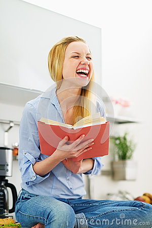 Smiling teenager girl reading book in kitchen