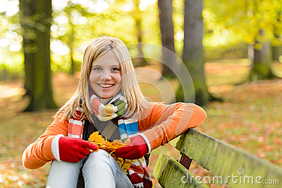 Smiling teenager girl sitting autumn park bench