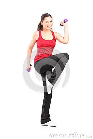 Smiling teenager lifting up a dumbbell