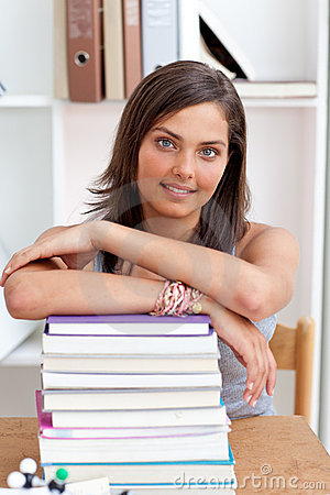 Smiling teenager studying lots of books