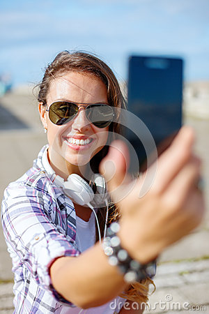 Smiling teenager taking picture with smartphone