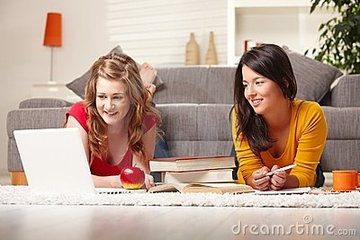 Smiling teens learning on floor