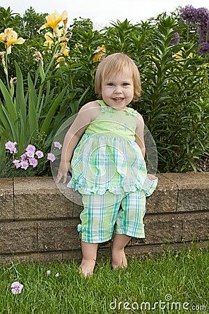smiling toddler in a garden