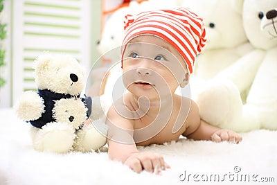 Smiling Toddler Wearing Orange And White Knit Cap Beside Black And White Bear Plush Toy Free Public Domain Cc0 Image