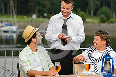 Smiling waiter taking order from men customers