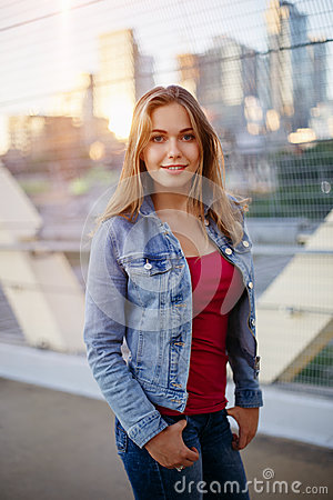 Free Smiling White Caucasian Girl Woman With Pony Tail, Wearing Jeans Jacket Outside In Evening Night City Street Bridge Royalty Free Stock Image - 95926106