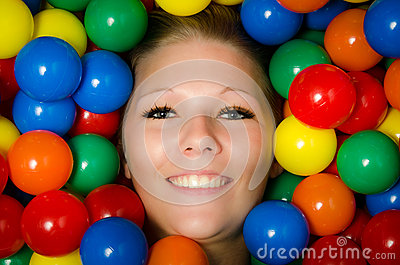 Smiling woman amongst colourful balls