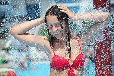 Smiling woman bathes in pool under water splashes