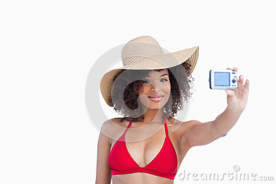Smiling woman in beachwear photographing herself