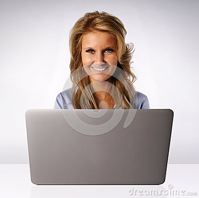 Smiling woman behind laptop computer