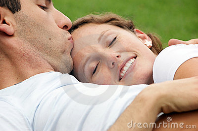 Smiling woman being kissed on forehead by husband