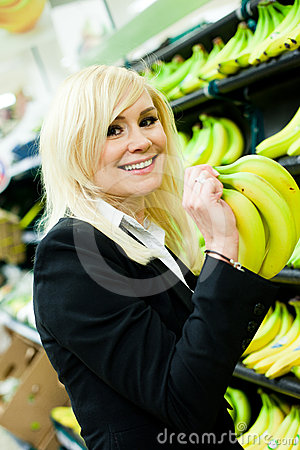 Smiling woman buying bananas