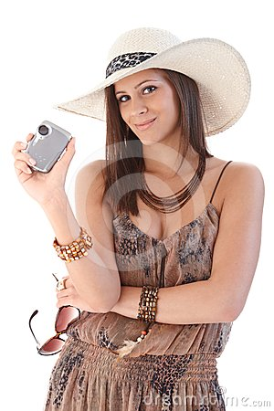 Smiling woman with camera at summertime