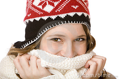 Smiling woman with cap holding scarf over mouth