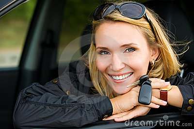 Smiling woman in car with keys