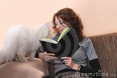 Smiling woman and cat reading book