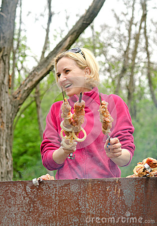 Smiling woman cooking kebabs over a BBQ fire Stock Photo