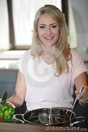 Smiling woman cooking in the kitchen