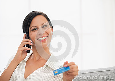 Smiling woman with credit card speaking mobile
