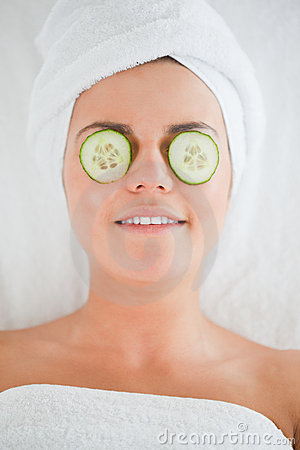 Smiling woman with cucumber slices on the face