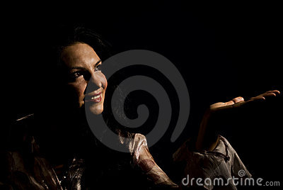 Smiling woman in dark make a presentation