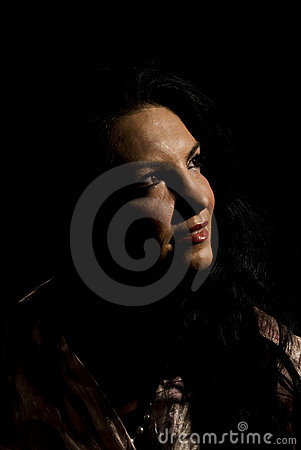 Smiling woman in darkness looking up