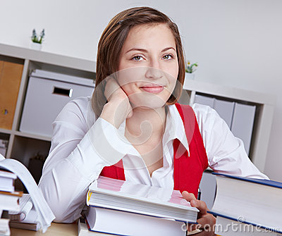 Smiling woman at desk with books