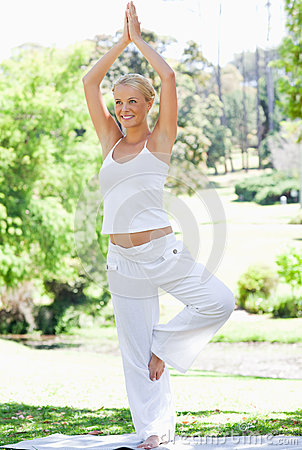 Smiling woman doing her yoga exercises