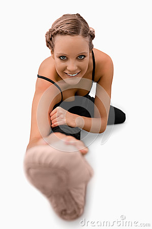 Smiling woman doing stretches on the floor