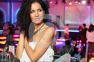 Smiling woman in dress looks away in night club.