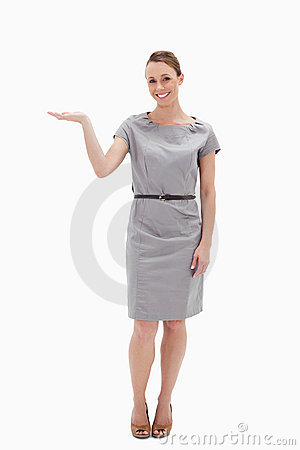 Smiling woman in a dress presenting something