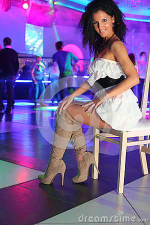 Smiling woman in dress sits on chair in night club
