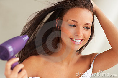 Smiling woman drying her hair with a blow dryer.