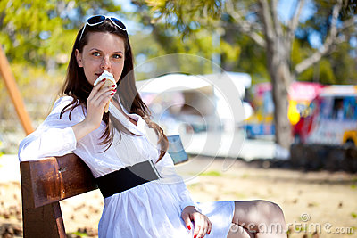 A smiling woman is eating an ice cream